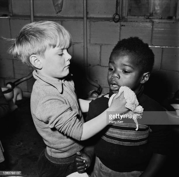 Two boys washing their faces at the Brixton Day Nursery on Coldharbour Lane in Brixton, south London, 1955. Four years earlier there were no Black...