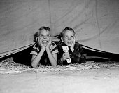 two boys watch circus from beneath