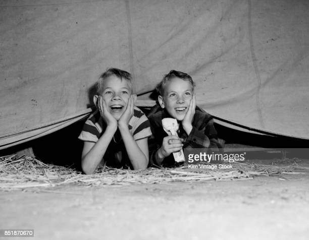 Two boys watch the circus after sneaking in, ca. 1950.