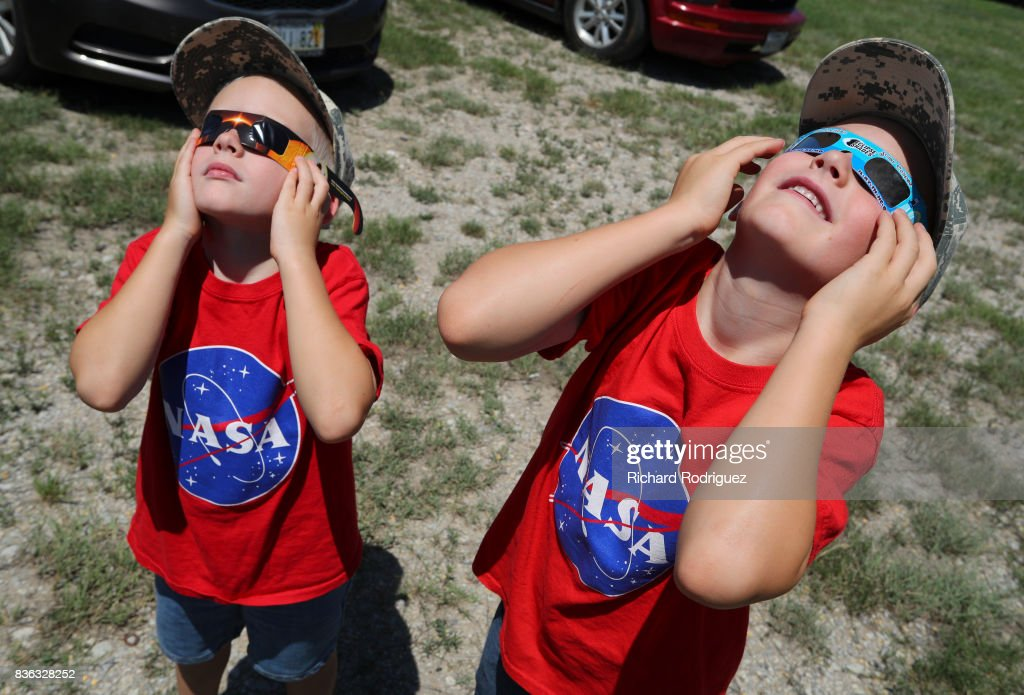 Two boys watch the solar eclipse at Texas Motor Speedway on August 21, 2017 in Fort Worth, Texas. Millions of people have flocked to areas of the U.S. that are in the 'path of totality' in order to experience a total solar eclipse. During the event, the moon will pass in between the sun and the Earth, appearing to block the sun. Fort Worth residents will see about 75 percent of the sun blocked by the moon.