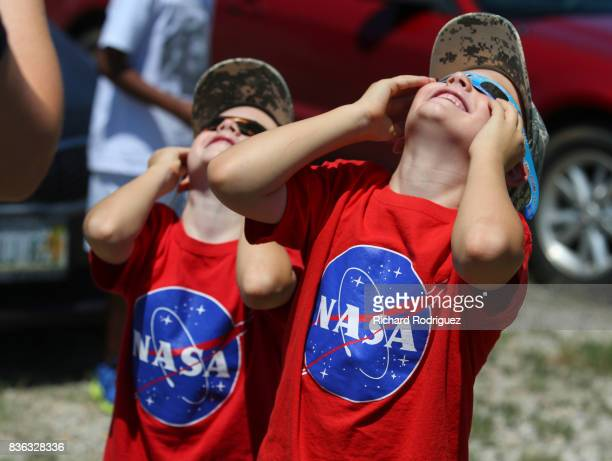 Two boys watch the solar eclipse at Texas Motor Speedway on August 21 2017 in Fort Worth Texas Millions of people have flocked to areas of the US...