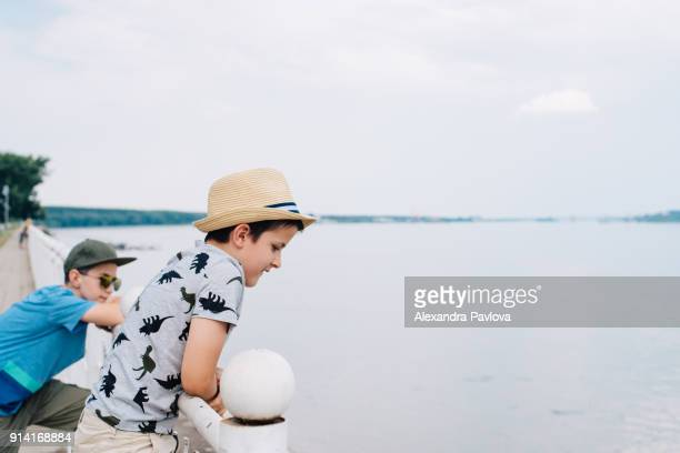 Two boys watching river, travelling together