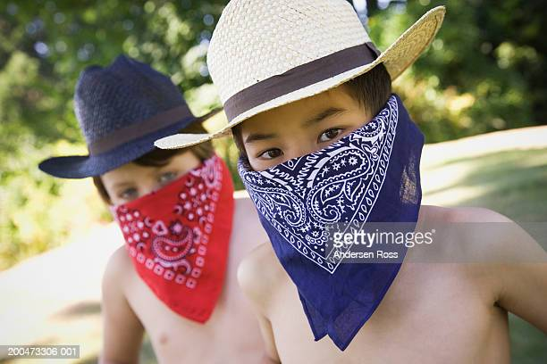 two boys (7-9) wearing cowboy hats and handkerchiefs over mouths - handkerchief stock photos and pictures