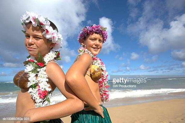 two boys (11-12) wearing grass hula skirts on beach, portrait - lei day hawaii stock pictures, royalty-free photos & images