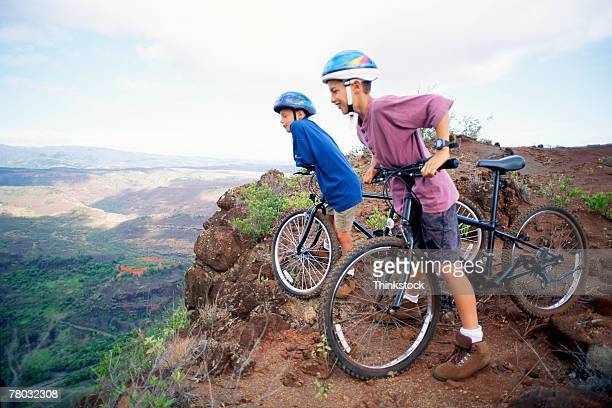 two boys wearing helmets stand with their bicycles overlooking the waimea canyon in kauai, hawaii. - waimea canyon stock pictures, royalty-free photos & images
