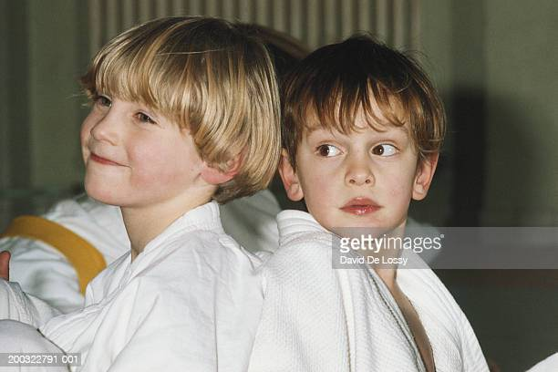 Two boys (4-7) wearing karate uniform, looking away, close-up