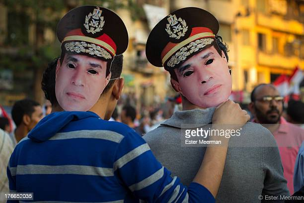 CONTENT] Two boys wearing masks of the Egyptian army general Abdel Fattah ElSisi on Tahrir Square on the 26th of July the day ElSisi called on the...