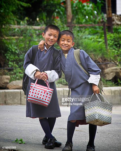 Two boys wearing national costume smiling and hugging for the picture. Thimphu, Bhutan