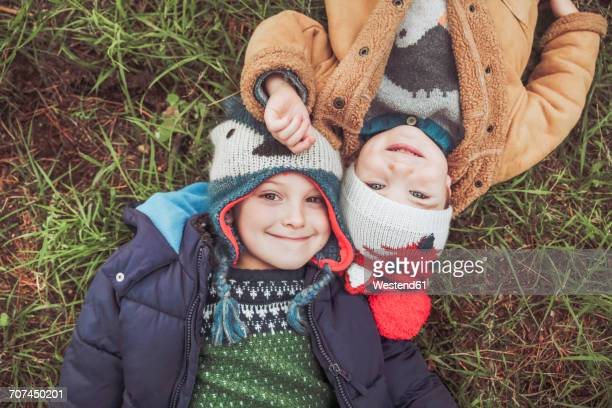Two boys wearing wooly hats lying in grass
