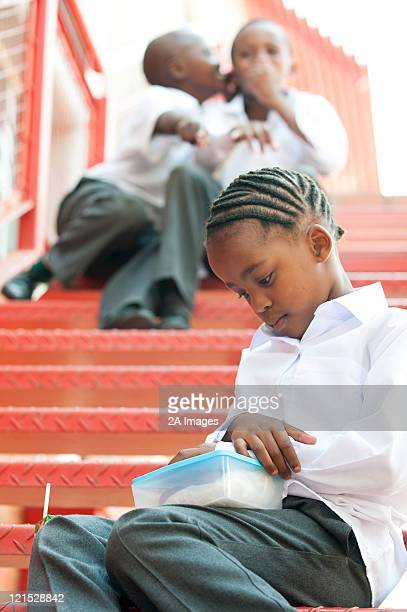 Two boys whispering about girl on steps outside school, Johannesburg, Gauteng Province, South Africa