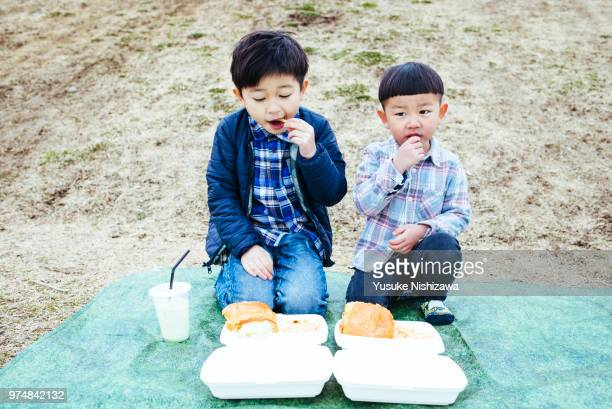two boys who eat french fries - yusuke nishizawa stock-fotos und bilder
