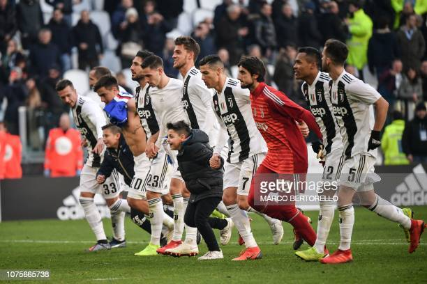 Two boys who took to the pitch after the game celebrate with Juventus' Portuguese forward Cristiano Ronaldo and teammates at the end of the Italian...