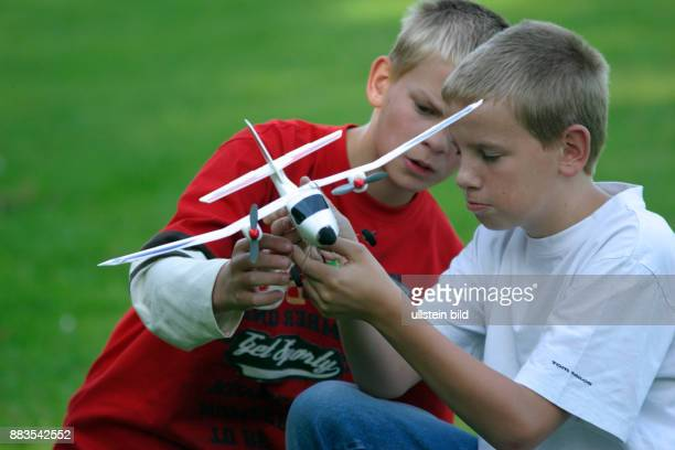 two boys with a remotecontrolled plane boy boys child children kid kids