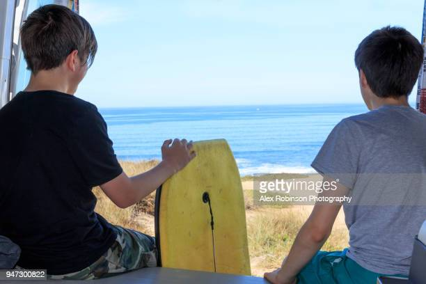 Two boys with a surfboard in a motorhome