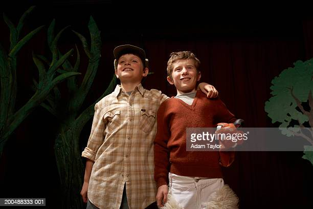 Two boys (9-11) with arms around each other on stage, smiling
