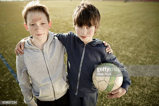 Two boys with ball on soccer field