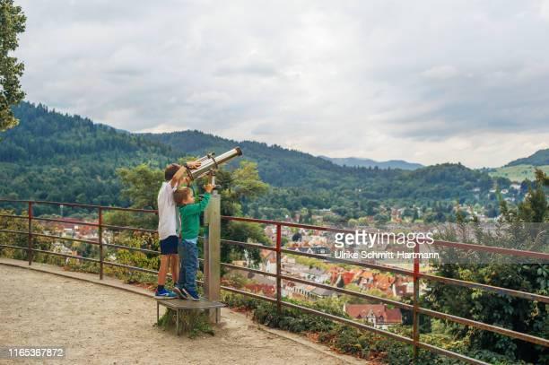 two boys with binoculars on viewpoint over city - freiburg im breisgau stock-fotos und bilder
