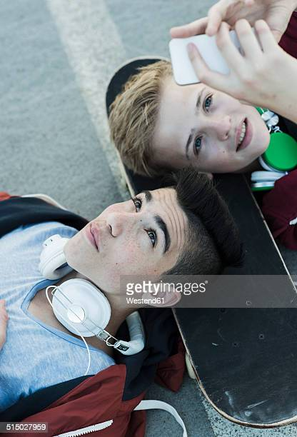 Two boys with cell phone and headphones lying on ground