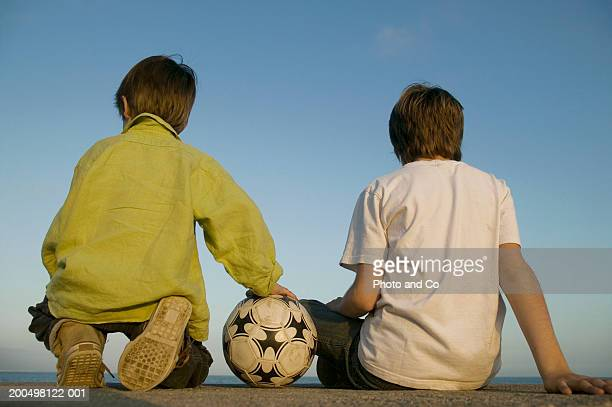 Two boys (5-10) with football, sitting outdoors