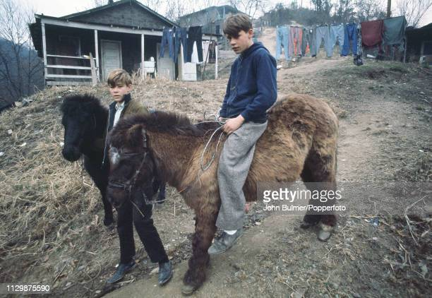 Two boys with ponies on a dirt road Pike County Kentucky US 1967