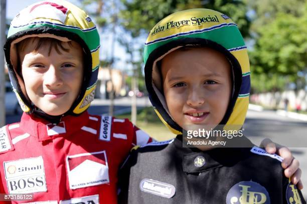 Two boys with the helmet colors of Ayrton Senna pose for photo before the final race of F1 GP Brazil at the Jose Carlos Pace racetrack in Sao Paulo...