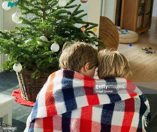 Two boys wrapped in blanket together