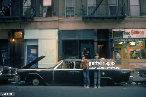 Two boys wrestle and play as they smile and try to hold still for a picture as they lean on a stripped car New York City September 1972
