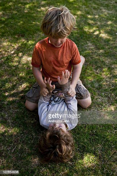 Two boys wrestling in the grass.