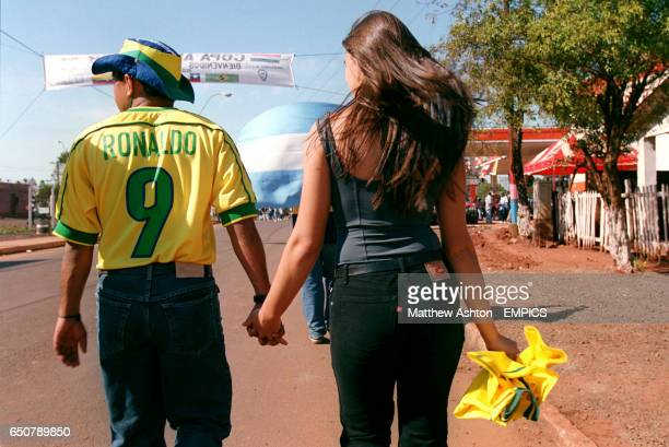 Two Brazilian fans walk to the Estadio 3 de Fevereiro in Cuidad Del Este Paraguay before the Copa America Quarter Final Brazil v Argentina