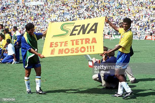 Two Brazilian players hold up a tribute to Formula One racing driver Ayrton Senna, who was killed in a crash in May 1994, at the 1994 FIFA World Cup...