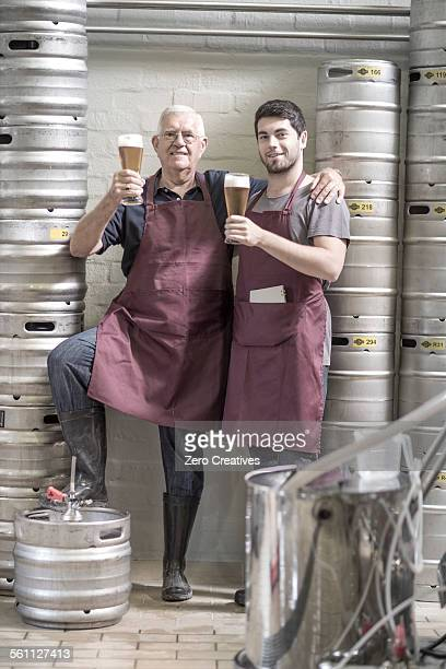 Two brewers drinking beer in the brewery, next to kegs