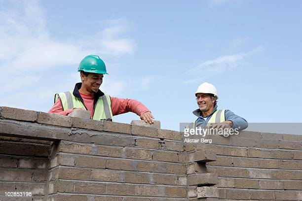 Two bricklayers building a wall
