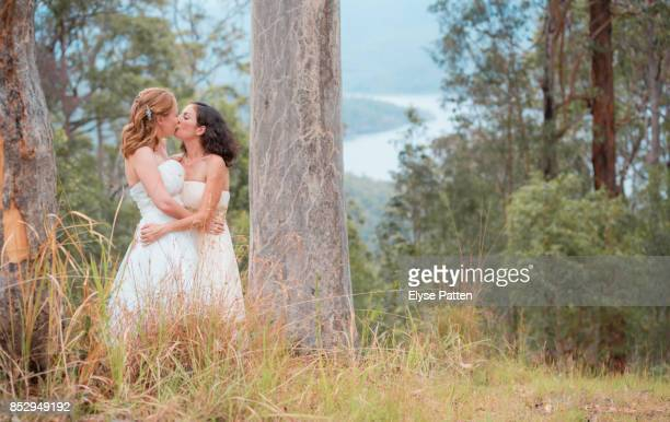 Two brides share a kiss after their wedding ceremony in Australia. The backdrop is an Australian bush scene.