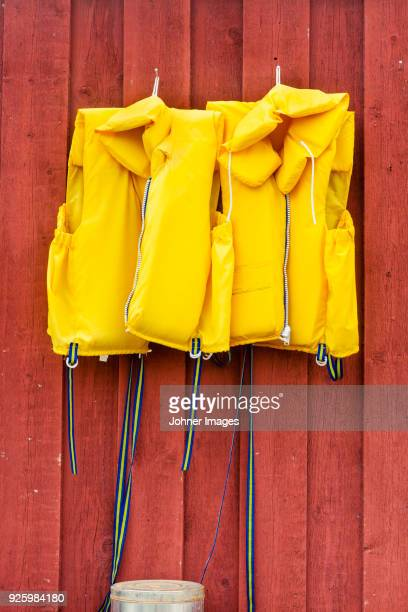 two bright yellow vests hanging on wooden wall - life jacket stock pictures, royalty-free photos & images