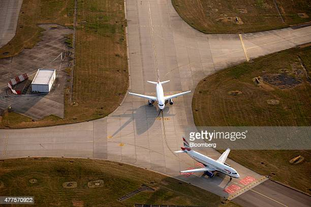 Two British Airways aircrafts operated by British Airways Plc stand on the perimeter of the runway at London Heathrow Airport in this aerial...