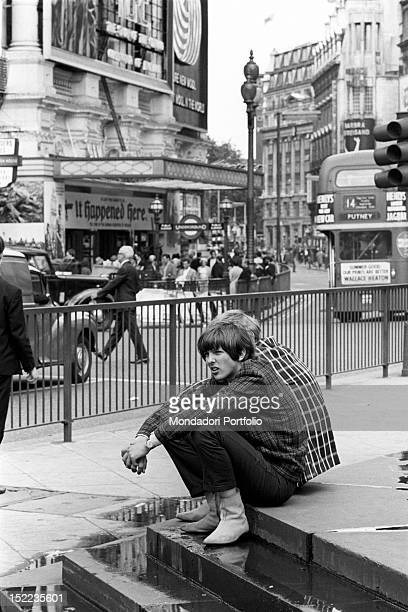 Two British boys sitting in Piccadilly Circus London 1960s
