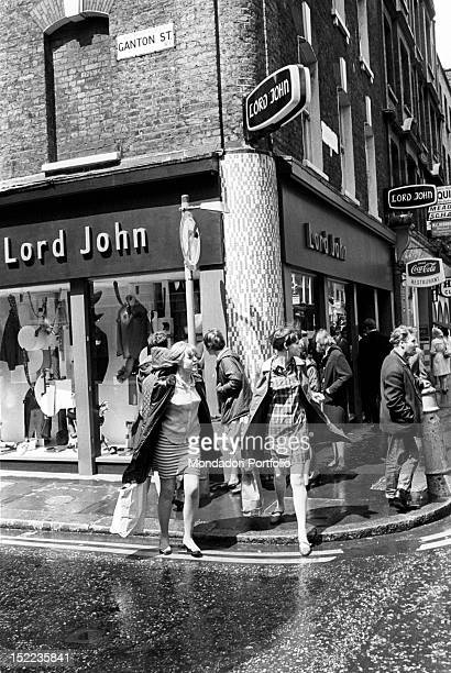 Two British girls in miniskirt crossing the road near the clothes shop 'Lord John' in Carnaby Street London 1960s
