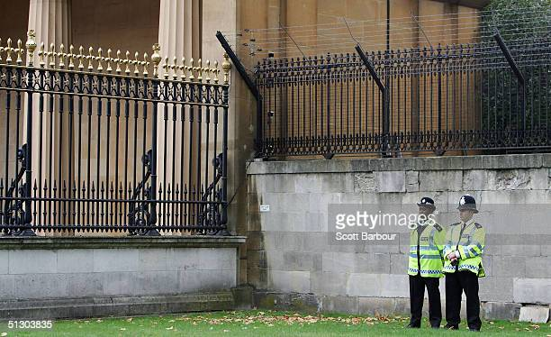 Two British police officers stand guard near the fence which protester Jason Hatch had used a ladder to climb over the previous day on September 14,...