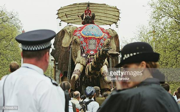 Two British police officers watch as a giant mechanical elephant walks along The Mall as part of The Sultan's Elephant show on May 6 2006 in London...