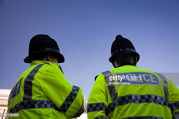 two british policemen wearing traditional helmets-click below for more. - groot brittannië stockfoto's en -beelden