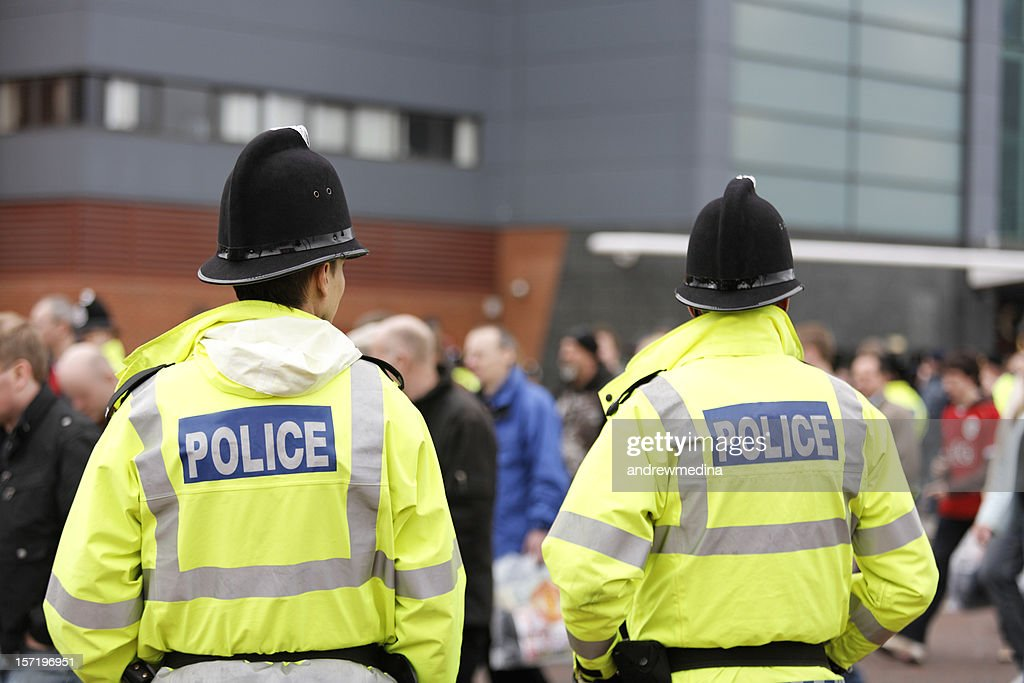 Two British Policemen-Traditional Helmets-Crowd Control. More below... : Stock Photo