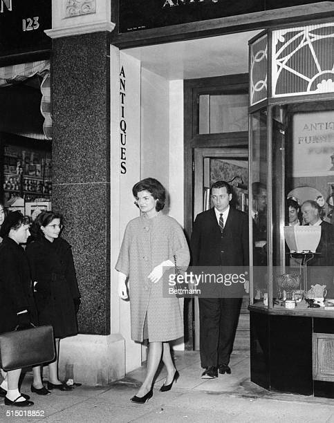 Two British schoolgirls cast admiring glances at America's First Lady Jacqueline Kennedy as she leaves the 'Nevillus and Skull' antique shop here...