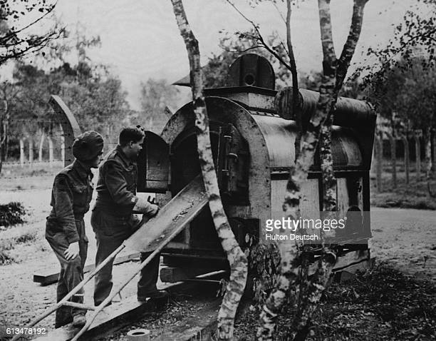 Two British soldiers at Hertogenbosch concentration camp, Holland, look at one of the three ovens in which the bodies of victims were cremated. |...