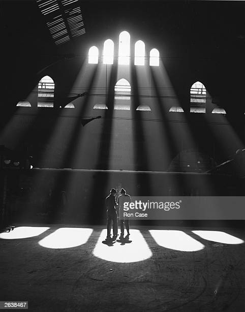 Two British soldiers stand in a shaft of sunlight streaming through a window, at London's Liverpool Street Station.