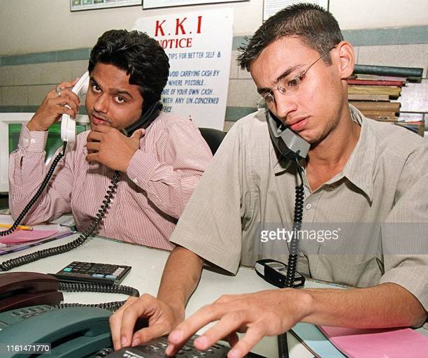 Two brokers place orders at the Karachi Stock Exchange after indices rose by over 21 points on 11 October 2001 Rumours kept depressing the market but...