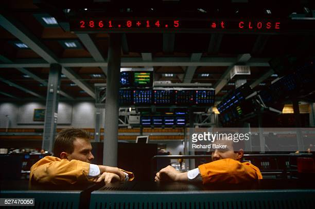 Two brokers working at the London International Financial Futures Exchange have finished trading for the day and are resting chatting to colleages...