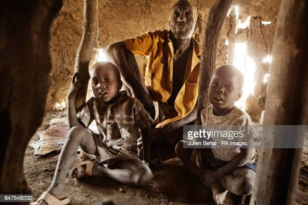 Two brothers and their blind grandfather in their Tukalor mud hutin a remote bush village along the Sobat River in the Greater Upper Nile region of...