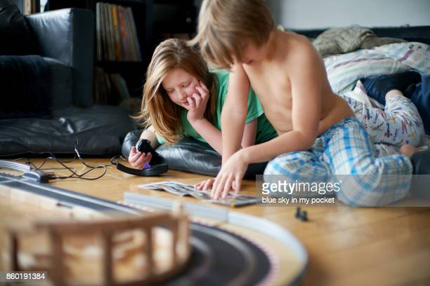 Two Brothers at home playing with slot cars.