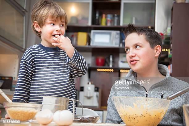 two brothers baking a cake together at home - chupando dedo - fotografias e filmes do acervo
