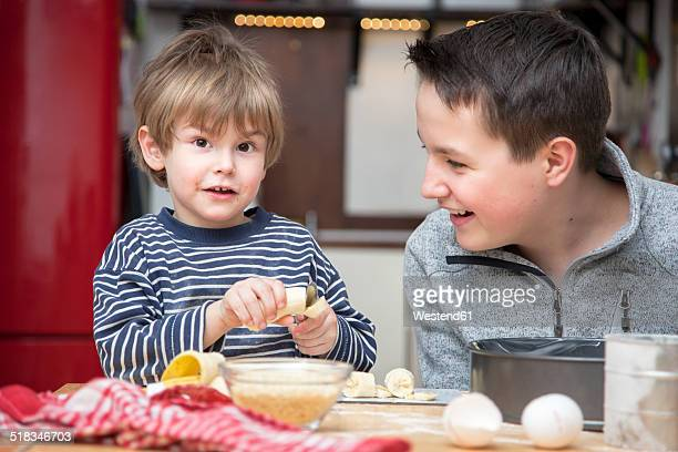 Two brothers baking a cake together at home